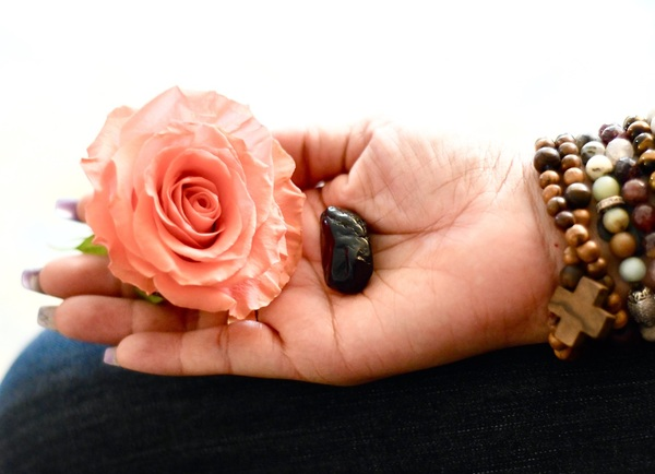Calming outstretched hand with a rose and black rock